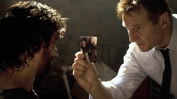 Bryan Mills in Taken holding a photograph of his daughter towards the person he believes has taken her.